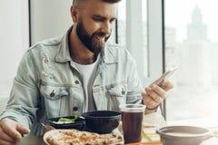 Le type de hippie s'assied en café à la table, prend le déjeuner, utilisant le smartphone L'homme paye l'ordre dans le restaurant image stock