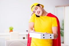 Le type de la livraison de pizza de super héros avec la couverture rouge Image stock