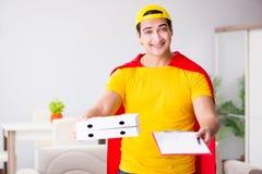 Le type de la livraison de pizza de super héros avec la couverture rouge Photographie stock libre de droits