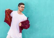 Le type de mode en verres pose près du mur la couleur de l'aigre photo libre de droits