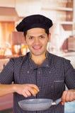 Le type de sourire tient une casserole dans la cuisine avec un oeuf dans sa main faisant cuire un plat, cuisine ecuatorian de chu Photographie stock libre de droits