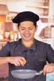 Le type de sourire tient une casserole dans la cuisine avec un oeuf dans sa main faisant cuire un plat, cuisine ecuatorian de chu Image stock