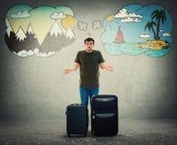 Le type de touristes embarrassé a des problèmes pour choisir la destination de vacances entre la mer et le voyage de montagnes photographie stock libre de droits