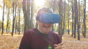 Le type dedans dans l'affichage tête-monté rit et a l'amusement en raison du jeu avec la réalité virtuelle, le hmd 360 banque de vidéos