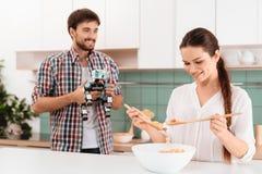 Le type donne à la fille de robot un rhinocéros La fille fait une salade et un sourire Image stock