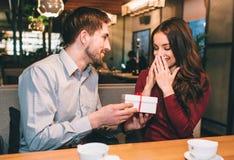 Le type donne à son amie un cadeau dans le boîtier blanc Elle le ` t de didn attendent cela Il aime rendre sa femme aimée heureus Photographie stock