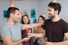 Le type donne à un ami une clé pour son anniversaire Derrière eux sont les filles de sourire Photographie stock libre de droits