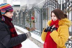 Le type donne une rose en hiver Photographie stock libre de droits