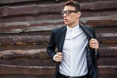 Le type enlève sa veste Élégant, beau, homme dans le costume classique, posant près du mur en bois Photographie stock libre de droits