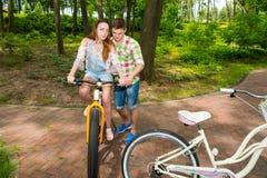 Le type enseigne son amie montant une bicyclette en parc Images stock