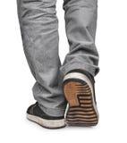 Le type entre dans les espadrilles noires et des jeans gris Photo stock