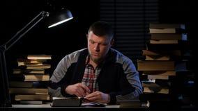 Le type entre et s'assied à la table avec des livres Fond noir banque de vidéos