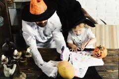 Le type et l'enfant avec les visages occupés dans des chapeaux décorent des potirons image stock