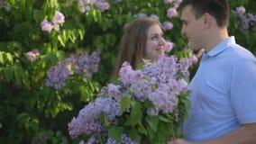 Le type et la fille affectueux avec un bouquet de lilas pendant l'été font du jardinage au coucher du soleil banque de vidéos