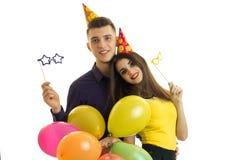 Le type et la fille avec des cônes sur leurs têtes semblent les verres de papier en avant et portants avec des ballons dans des m Photos libres de droits