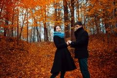 Le type et la fille gais pendant l'automne se garent, tenant des mains Photos libres de droits