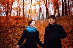 Le type et la fille gais pendant l'automne se garent, tenant des mains Image libre de droits