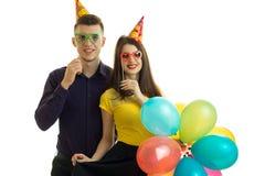 Le type et la fille heureux avec des verres et des ballons colorés semblent en avant et sourire Image stock