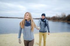 Le type et la fille marchent sur une plage d'automne de désert image libre de droits
