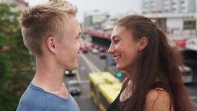 Le type et la fille regardent l'un l'autre avec les yeux affectueux la rue de ville banque de vidéos