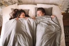 Le type et la fille se trouvent sur le lit sous les couvertures grises et regardent l'un l'autre photos libres de droits