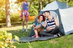 Le type et la gamine tatoués repose et boit de la bière devant la tente Photo libre de droits