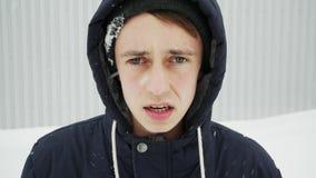 Le type fâché après un combat sous les chutes de neige, avec une lésion oculaire respire fortement banque de vidéos