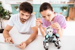 Le type fait le robot dans la cuisine Son amie se tient à côté de lui et l'aide Images libres de droits