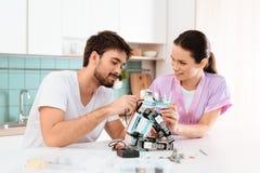 Le type fait le robot dans la cuisine Son amie se tient à côté de lui et l'aide Image stock