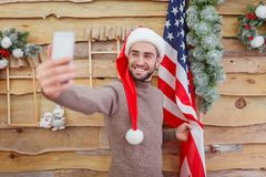 Le type fait le selfie avec le drapeau américain au mur Front View Photo stock