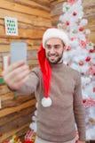 Le type fait le selfie avec l'arbre de Noël dans la chambre Image stock