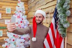 Le type fait le selfie avec un drapeau américain contre le contexte d'un arbre de Noël décoré Vue de côté Photographie stock