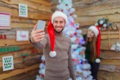Le type fait le selfie sur le fond d'une fille à un arbre de Noël dans une chambre avec des photos Image libre de droits