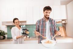 Le type fait une salade Une fille qui tient un robot de rhinocéros l'approche Le type et la fille sourient Images stock