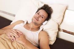 Le type futé se situe dans le lit et écoute la musique Image stock