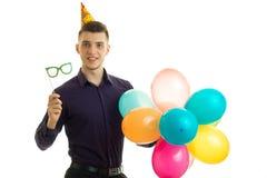 Le type gai beau avec un cône sur sa tête tient des lunettes de soleil et des boules colorées par air Images stock