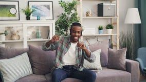 Le type heureux d'Afro-américain est dansant et chantant écouter la musique par des écouteurs se reposant sur le divan à la maiso banque de vidéos
