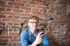 Le type heureux de hippie a reçu de bonnes actualités sur le téléphone portable portatif photo stock