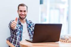 Le type heureux s'asseyant en café avec l'ordinateur portable et montrant le pouce font des gestes  Images libres de droits
