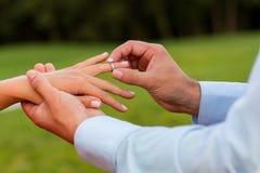 Le type met l'anneau sur le doigt de son amie Photo libre de droits