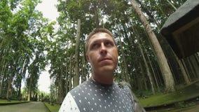 Le type mignon caucasien se tient en parc avec le singe gris grimpant sur son corps banque de vidéos