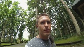 Le type mignon caucasien se tient en parc avec le singe se reposant sur sa tête et épaules banque de vidéos