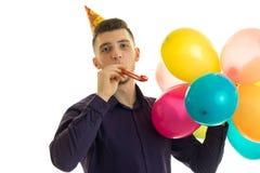 Le type mignon drôle avec un cône sur sa tête regardant directement se tient dans sa main et souffle des boules en plan rapproché Photographie stock