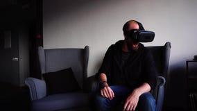 Le type mignon immergé dans la réalité virtuelle et s'assied en café élégant le jour d'hiver