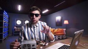 Le type mignon parle à la caméra ayant la boîte d'alimentation d'énergie avec le refroidisseur mis sur le bureau banque de vidéos