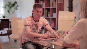 Le type mignon s'assied à la table avec la jeune femme blonde, tient la tasse de thé, regarde autour banque de vidéos