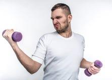 Le type mince tient des haltères dans des ses mains Il essaye de gagner quelques muscles avant des étés viendra Il veut à photo stock