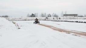Le type monte un ATV sur une route couverte de neige en hiver banque de vidéos