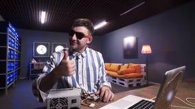 Le type montre le pouce jusqu'à la caméra ayant la boîte d'alimentation d'énergie avec le refroidisseur mis sur le bureau clips vidéos