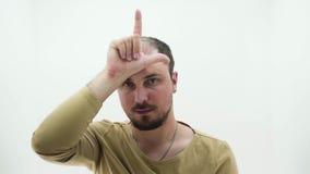Le type montre le symbole de perdant sur le fond blanc banque de vidéos